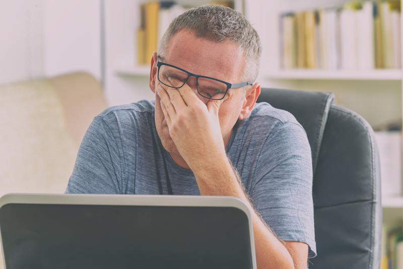 Bespectacled man at his laptop, covering his eyes with his left hand.