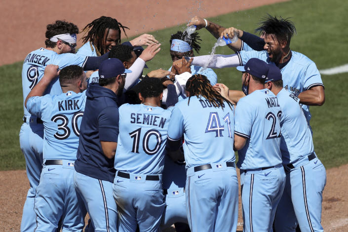 Members of the Toronto Blue Jays celebrate a game-winning home run against the New York Yankees during the ninth inning of a baseball game Wednesday, April 14, 2021, in Dunedin, Fla. The Blue Jays won 5-4. (AP Photo/Mike Carlson)