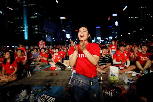 A woman reacts as she watches the broadcast of the World Cup Group F soccer match between Sweden and South Korea, in central Seoul, South Korea, June 18, 2018. REUTERS/Kim Hong-Ji