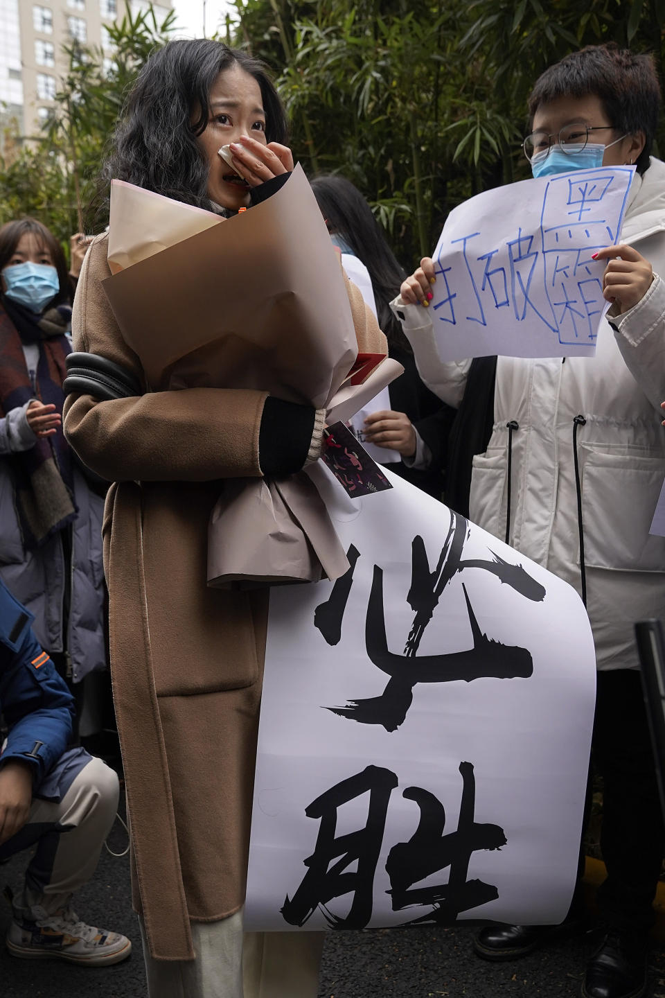 "Zhou Xiaoxuan, left, holds a banner which reads ""Must Win"" as she arrives at a courthouse in Beijing, Wednesday, Dec. 2, 2020. Zhou, a Chinese woman who filed a sexual harassment lawsuit against a TV host, told dozens of cheering supporters at a courthouse Wednesday she hopes her case will encourage other victims of gender violence in a system that gives them few options to pursue complaints. (AP Photo/Andy Wong)"