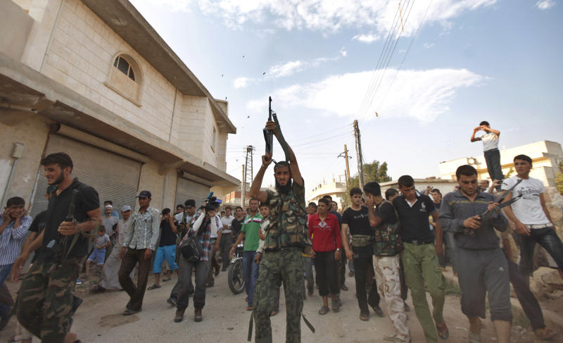 A Syrian gunman shoots on the air during the funeral of 29 year-old Free Syrian Army fighter, Husain Al-Ali, who was killed during clashes in Aleppo, in the town of Marea on the outskirts of Aleppo city, Syria, Thursday, Aug. 9, 2012. (AP Photo/ Khalil Hamra)