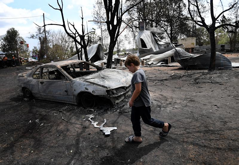 Eight year-old Jarrod McInnes walks next to the remains of a house that his family was about to buy and was destroyed by bushfires in Rappville, NSW.