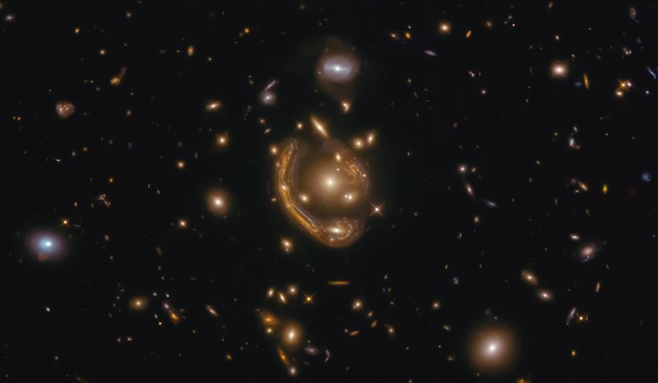 "This image, taken by the NASA/ESA Hubble Space Telescope, shows the Einstein ring GAL-CLUS-022058s. Einstein rings are created when the light from distant objects like galaxies pass by an extremely massive object. Because of the process known as gravitational lensing, this light is bent and distorted into this amazing, bright curve or ""ring."" Scientists can use these rings to study galaxies that might otherwise be too faint or far away to see."