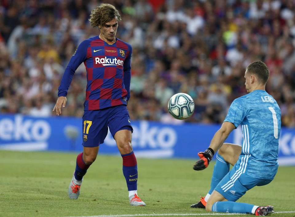 FC Barcelona's Antoine Griezmann, left, vies for the ball with Arsenal's goalkeeper Bernd Leno during the Joan Gamper trophy soccer match between FC Barcelona and Arsenal at the Camp Nou stadium in Barcelona, Spain, Sunday, Aug. 4, 2019. (AP Photo/Joan Monfort)