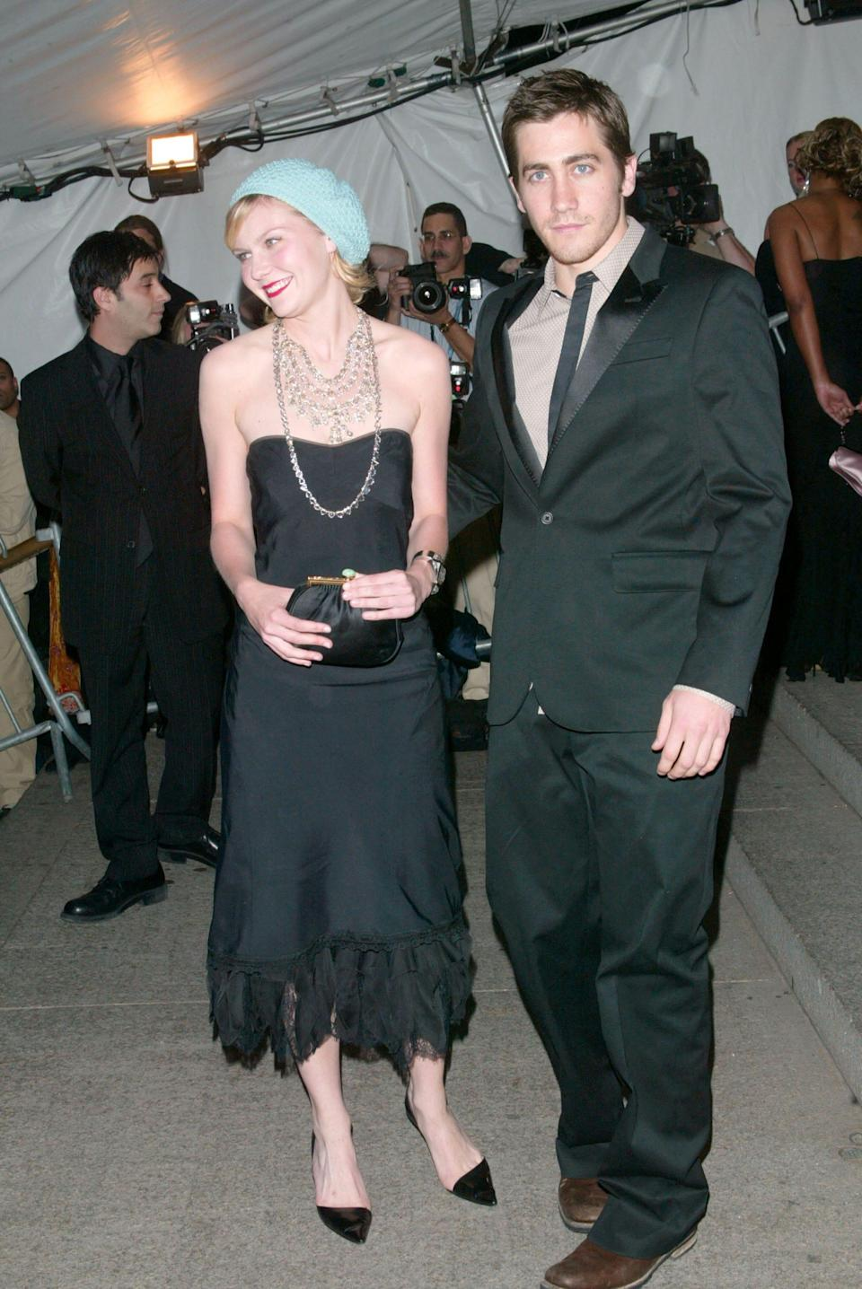 Kirsten Dunst in a black dress and hat and Jake Gyllenhaal in a suit on a red carpet.
