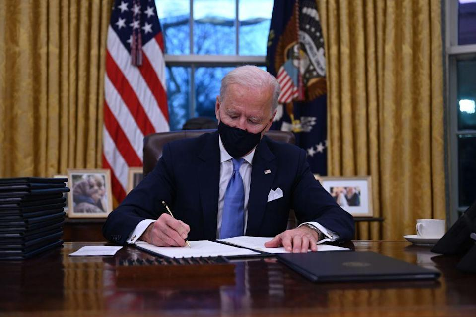 """<p>In between being sworn in on the steps of the Capitol and watching a primetime concert to celebrate his new presidency, Biden got straight to work - heading to the Oval Office to sign several Executive Orders.</p><p>Among them were: Mandating the wearing of masks on federal property to protect people from Coronavirus, re-joining the Paris Climate Change agreement which Donald Trump controversially pulled the US out of, ended an Trump-ordered travel ban from Muslim-majority countries and stopped the funding of that infamous 'wall' between the US and Mexico, <a href=""""https://www.bbc.co.uk/news/world-us-canada-55738746"""" rel=""""nofollow noopener"""" target=""""_blank"""" data-ylk=""""slk:reports the BBC."""" class=""""link rapid-noclick-resp"""">reports the BBC.</a></p>"""