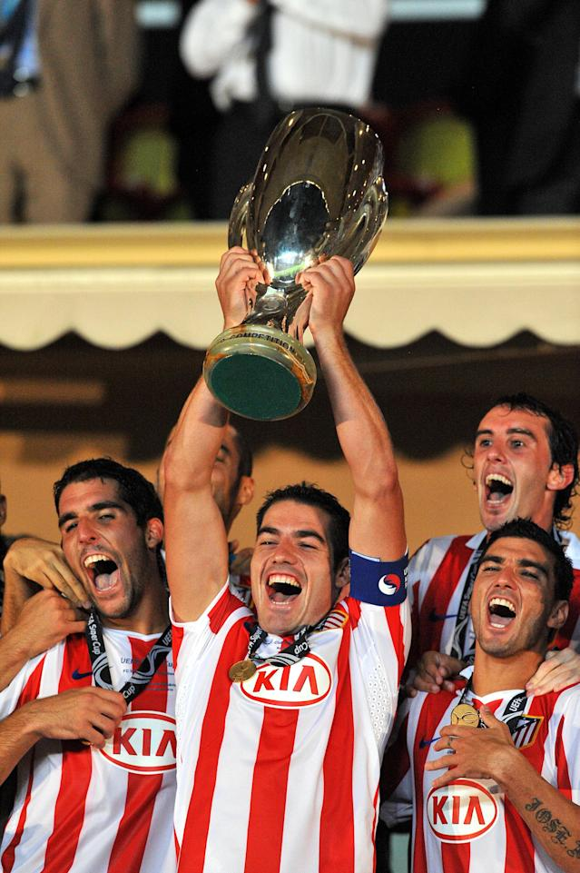 Atletico Madrid's Antonio Lopez (holding cup) celebrates Super Cup victory with Raul Garcia (left) and Reyes (right) (Photo by Neal Simpson - EMPICS/PA Images via Getty Images)