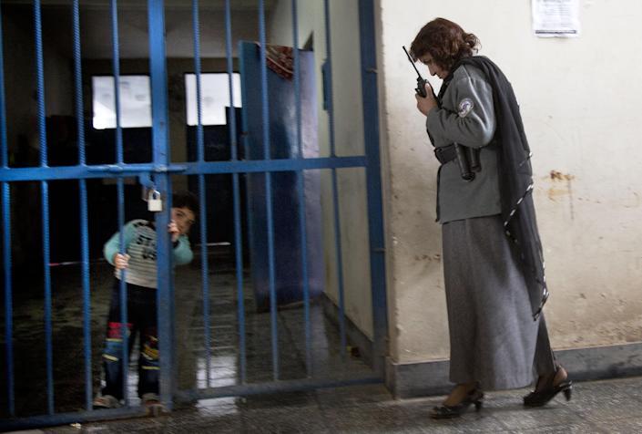 """Picture taken March 28, 2013 shows an Afghan prisoner guard taking on the walking talkie as a young boy peers through the prison bars at Badam Bagh, Afghanistan's central women's prison, in Kabul, Afghanistan. Sixty-two children living with their imprisoned mothers in the six- year- old jail, the majority of the mothers are serving sentences of up to seven years for leaving their husbands, refusing to accept a marriage arranged by their parents, or choosing to leave their parent's home with a man of their choice, all so-called """"moral"""" crimes(. AP Photo/Anja Niedringhaus)"""