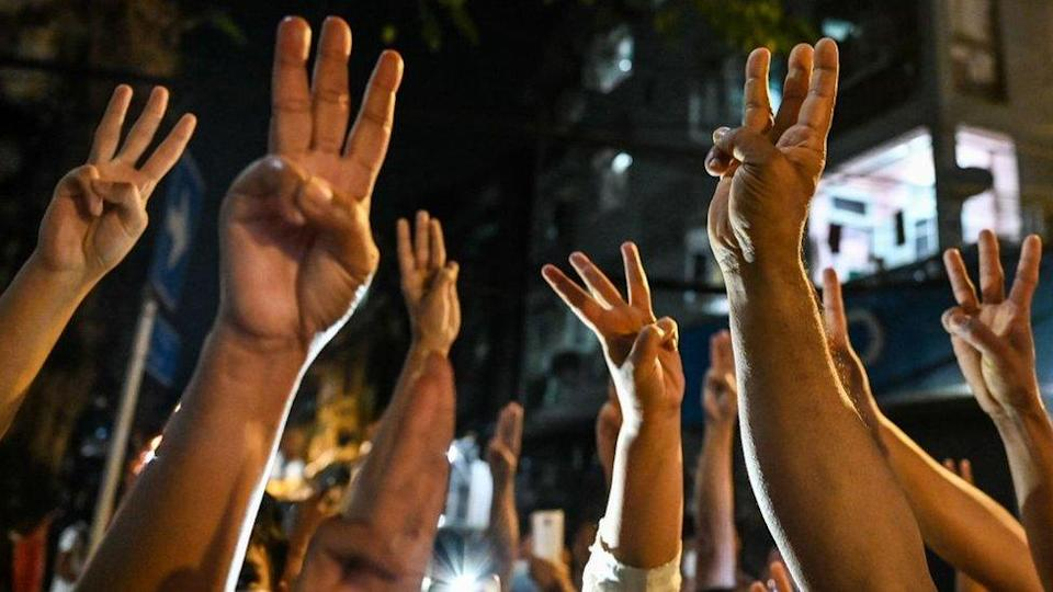 People give a three-finger salute at a protest in Yangon