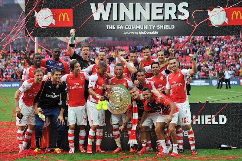 Arsenal players with the Community Shield trophy after they won the FA Community Shield against Manchester City at Wembley Stadium on August 10, 2014 (AFP Photo/Glyn Kirk)