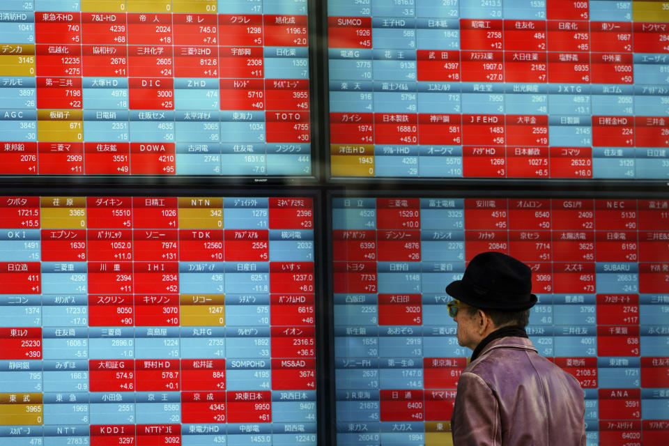 A man looks at an electronic stock board showing Japan's Nikkei 225 index at a securities firm in Tokyo Tuesday, Jan. 14, 2020. Asian shares followed Wall Street higher on Tuesday amid optimism that a trade deal between the U.S. and China will be a boon for the regional economy. (AP Photo/Eugene Hoshiko)