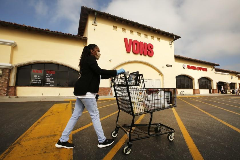 TORRANCE, CA - APRIL 27: Vons shopper Marcena Mitchell finishes her shopping in the morning at the Vons located at 24325 Crenshaw Blvd in Torrance. Doors to the store opened at 6 a.m. for seniors and at-risk shoppers due to the Coronavirus and at 7 a.m. for regular customers. Most of the team arrives at 5 a.m. to stock the shelves with product, sanitize the location for staff and shoppers, and picker/shoppers begin to collect items for .com home delivery shoppers. Vendors arriving throughout the morning must read a checklist of warnings, sign in and they must wear face covering. Vons on Monday, April 27, 2020 in Torrance, CA. (Al Seib / Los Angeles Times)