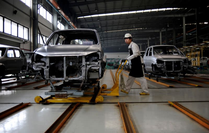 FILE PHOTO - An employee pushes a car along a Zotye Automobile Co., Ltd assembly line in Jinhua