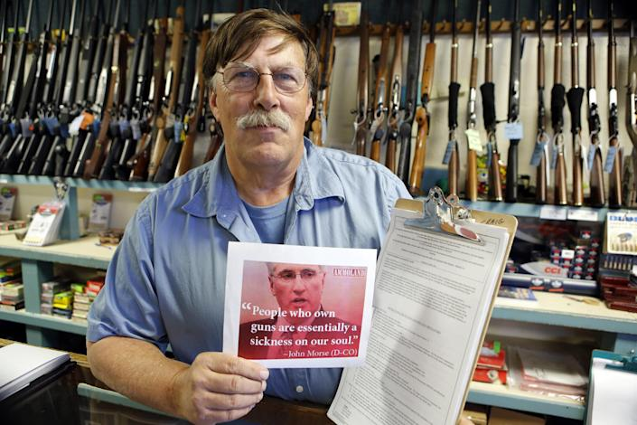 In this photo taken May 24, 2013, Paradise Firearms owner Paul Paradis holds a flyer depicting Colorado's State Senate President, Democrat John Morse, together with a petition to recall him, right, at his gun shop in Colorado Springs, Colo. Paradis and other gun-rights activists are seeking the ouster of Morse for his support of new laws that restrict ammunition magazines and expand background checks to include private gun sales. (AP Photo/Ed Andrieski)