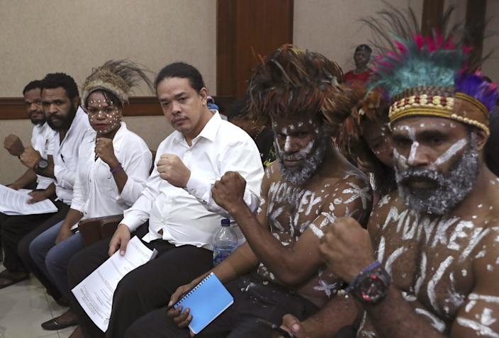 "Papuan independence activists, from left, Isay Wenda, Charles Kossay, Suryanta Ginting, Arina Elopere, Ambrosius Mulait and Anes Tabuni, show their solidarity before the start of their trial in Jakarta, Indonesia, on Dec. 19, 2019. The activists were charged with treason after a rally against racism and advocating independence for their restive region. <span class=""copyright"">(Tatan Syuflana / Associated Press)</span>"