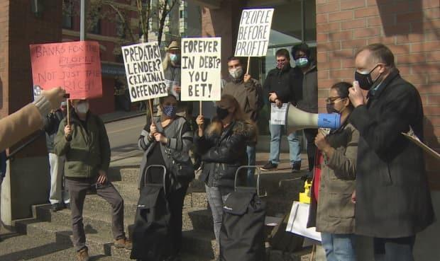 People gather at a payday loan protest in New Westminster on Saturday March 13, 2021.