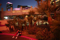 A woman sits on a curb along the Strip in Las Vegas, Feb. 10, 2021. Visitor numbers in Las Vegas were down by more than half in 2020 compared to 2019, according to data compiled by tourism, airport and gambling regulators. (AP Photo/John Locher)