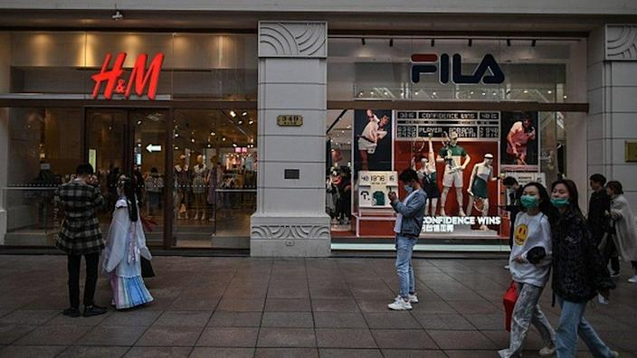 People pass by the storefront of Swedish clothing giant H & amp; M
