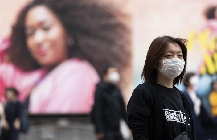 A woman wearing a face mask waits for the traffic lights to change at the famed Shibuya crossing in Tokyo on Thursday, May 20, 2021. (AP Photo/Hiro Komae)