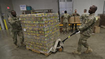Ohio National Guard Specialist Scott Eubanks, right, and Corp. Tommie Davis move a skid of peaches to prepare for repackaging emergency food boxes for food distribution at the Cleveland Food Bank, Tuesday, March 24, 2020, in Cleveland. (AP Photo/Tony Dejak)