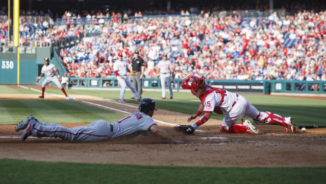 Washington Nationals' Ryan Zimmerman, left, scores past Philadelphia Phillies catcher Andrew Knapp on a two-run single by Victor Robles during the first inning of a baseball game, Friday, July 12, 2019, in Philadelphia. (AP Photo/Matt Slocum)