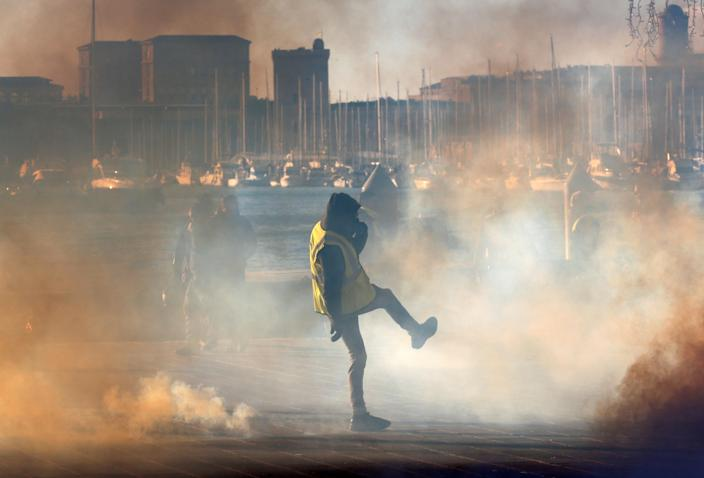 """A yellow vest protester walks among tear gas during clashes with French Gendarmes at a demonstration of the """"yellow vests"""" movement in Marseille, France, Dec. 8, 2018. (Photo: Jean-Paul Pelissier/Reuters)"""