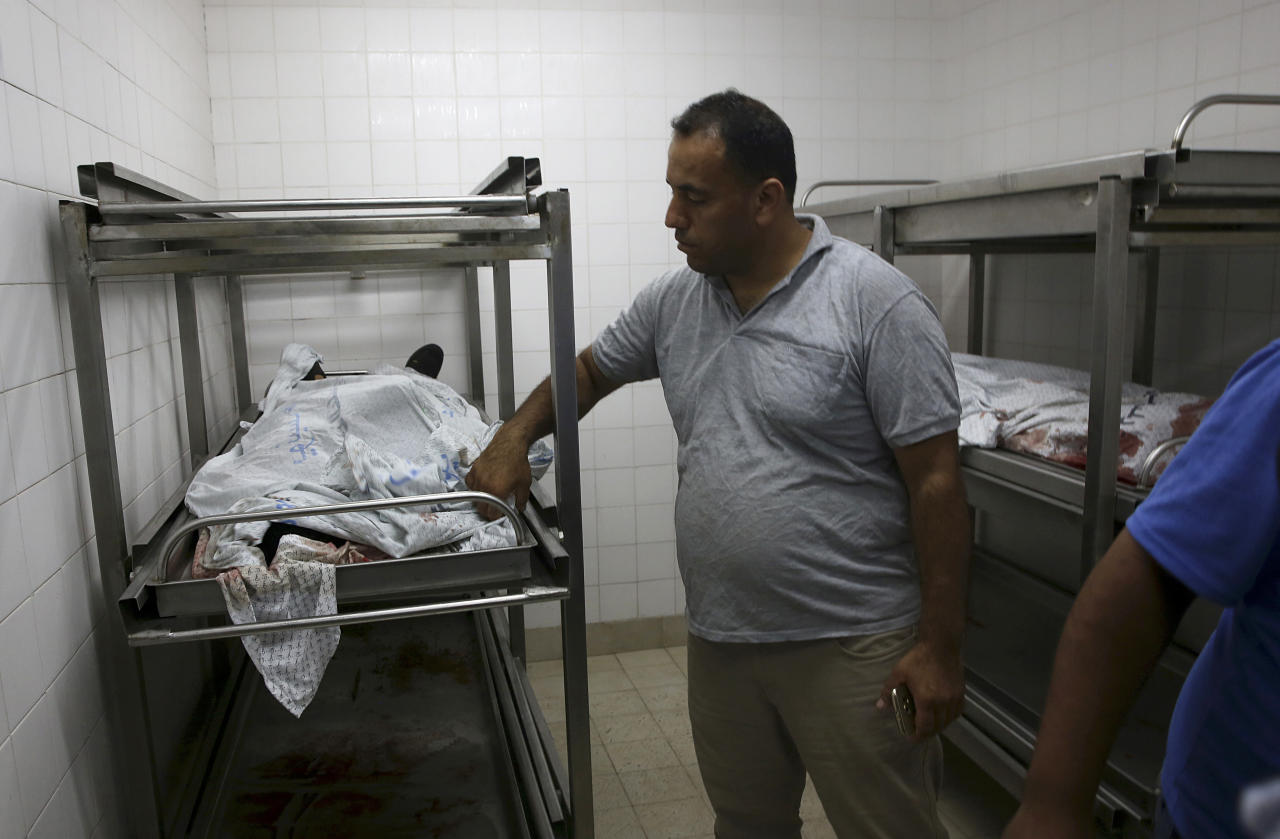 A medic covers the bodies of militants at the morgue of the European hospital east of Khan Younis, southern Gaza Strip, Friday, July 20, 2018. Israel pummeled Hamas targets in Gaza killing four Palestinians on Friday in a series of air strikes after gunmen shot at soldiers near the border, officials said. The Gaza Health Ministry said four Palestinians were killed. The militant Islamic Hamas that rules Gaza said three of the dead were members of the group. (AP Photo/Adel Hana)