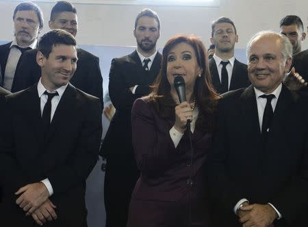 Argentine President Cristina Fernandez de Kirchner (C) speaks next to soccer player Lionel Messi (L) and coach Alejandro Sabella (R) as Argentina's national soccer team arrives at the Argentine Football Association (AFA) in Buenos Aires, in this July 14, 2014 handout picture provided by the Argentine Presidency. REUTERS/Argentine Presidency/Handout via Reuters