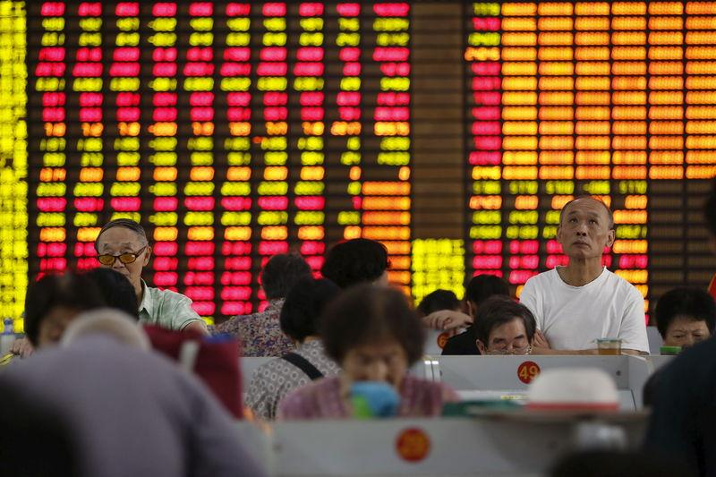 Investors look at computer screens showing stock information at a brokerage in Shanghai