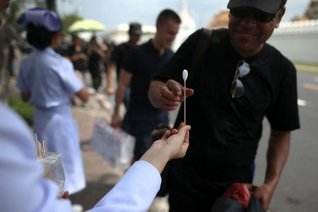 A mourner receives ammonia-soaked cotton wool handed out by medical rescue teams to help prevent fainting as he waits to pay his respects to Thailand's late King Bhumibol Adulyadej at the Grand Palace in Bangkok, Thailand, October 15, 2016. REUTERS/Athit Perawongmetha