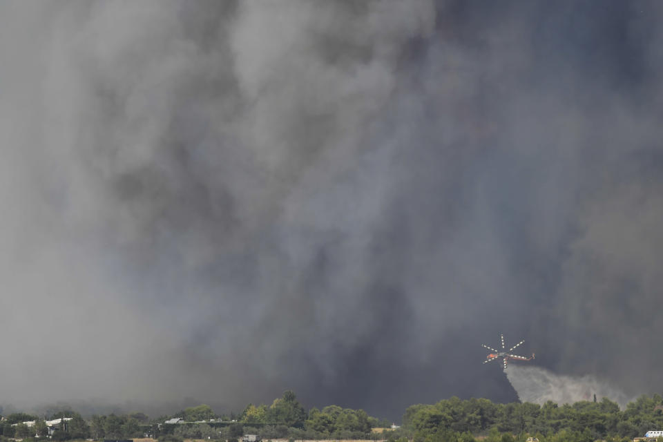 A helicopter of the Greek Fire Service drops water during a wildfire that broke out in Tatoi, northern Athens, Greece, Tuesday, Aug. 3, 2021. The Greek Fire Service maintained an alert for most of the country Tuesday and Wednesday, while public and some private services shifted operating hours to allow for afternoon closures. (AP Photo/Michael Varaklas)