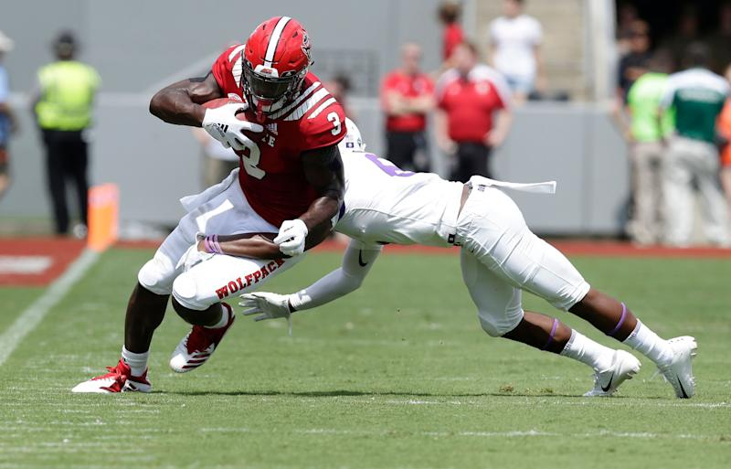 North Carolina State's Kelvin Harmon (3) runs the ball while James Madison's Jimmy Moreland dives for the tackle during the first half an NCAA college football game in Raleigh, N.C., Saturday, Sept. 1, 2018. (AP Photo/Gerry Broome)