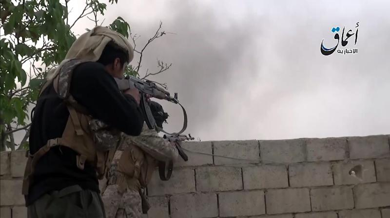 An image from a video posted on YouTube on October 19, 2014 by Aamaq News, allegedly shows IS militants taking shooting positions in the town Kobane (AFP Photo/)
