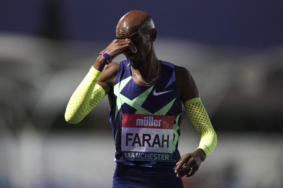 Britain's Mo Farah reacts after failing to achieve the qualifying time in the Men's 10000m final during day one of the British Athletics Championships at Manchester Regional Arena in England, Friday June 25, 2021. Mo Farah failed to qualify for the Tokyo Olympics and will not defend his 10,000-meter title. The four-time Olympic champion missed the qualifying time in an invitational 10,000 at the British athletics championships in Manchester. (Martin Rickett/PA via AP)