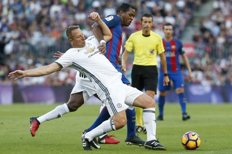 Dutch former Barcelona forward Patrick Kluivert (R) tackles ex-Manchester United defender Lee Martin during a charity match between Barcelona Legends and Man United Legends at the Camp Nou stadium in Barcelona on June 30, 2017