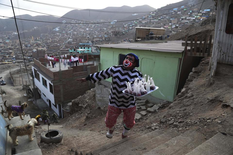 """Circus clown Jhona Zapata, whose clown name is """"Jijolin,"""" offers caramelized apples for sale during the lockdown to curb the spread of COVID-19 in a poor neighborhood on the outskirts of Lima, Peru, Wednesday, Aug. 5, 2020. Zapata, 35, is selling circus food to help his family survive the economic shutdown. (AP Photo/Martin Mejia)"""