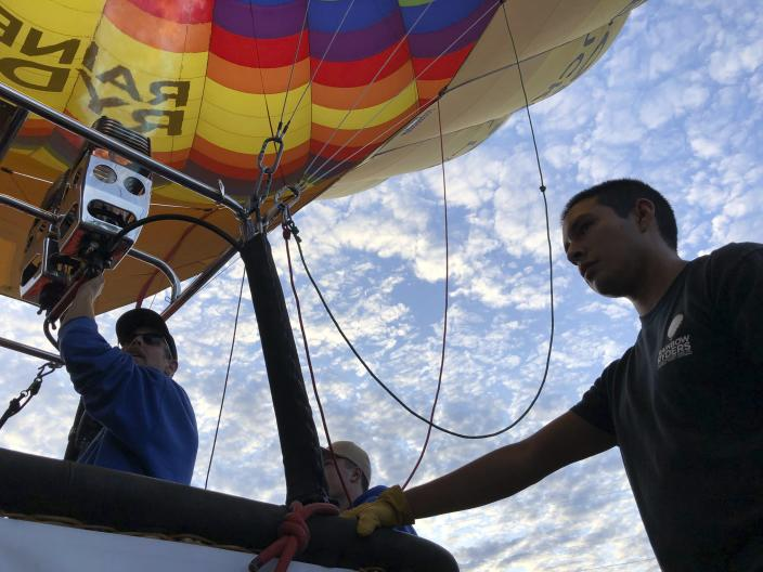 Elijah Sanchez, right, helps pilot Troy Bradley, left, prepare for liftoff in Albuquerque, N.M., on Tuesday, Oct. 1, 2019. Sanchez, 20, will be among the youngest pilots to launch as part of this year's Albuquerque International Balloon Fiesta. The nine-day event is expected to draw several hundred thousand spectators and hundreds of balloonists from around the world. It will kick off Oct. 5 with a mass ascension. (AP Photo/Susan Montoya Bryan)