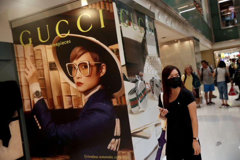 FILE PHOTO: A woman walks past a Gucci advertising poster as shoppers and anti-government protesters gather at New Town Plaza in Sha Tin, Hong Kong