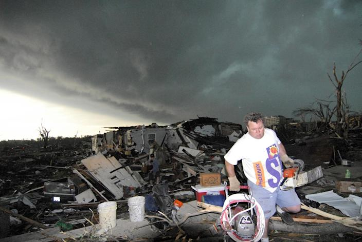 FILE - In this May 23, 2011, file photo Mark Siler carries salvaged items from the house of a friend following a devastating tornado in Joplin, Mo. The National Weather Service is kicking off an experiment next week with a new kind of tornado warning that's aimed to scare people into seeking shelter. (AP Photo/Mike Gullett, File)