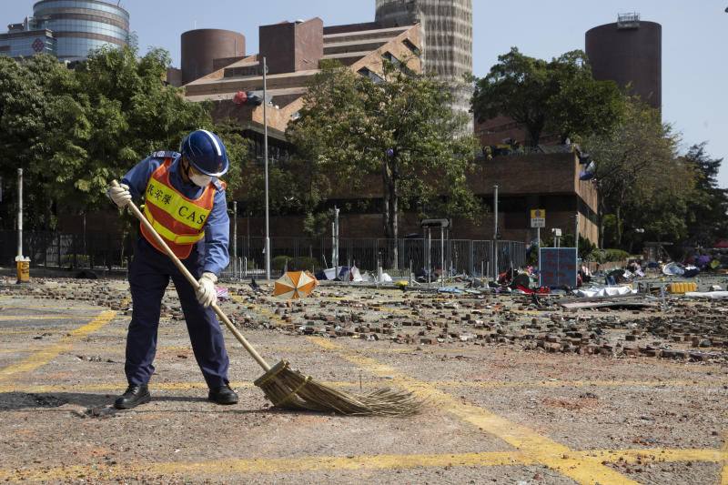 A worker sweeps the road outside the Polytechnic University in Hong Kong on Wednesday, Nov. 20, 2019. A small group of protesters refused to leave Hong Kong Polytechnic University, the remnants of hundreds who took over the campus for several days. They won't leave because they would face arrest. Police have set up a cordon around the area to prevent anyone from escaping. (AP Photo/Ng Han Guan)
