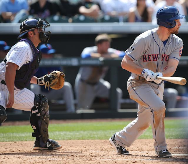 New York Mets' Daniel Murphy, right, follows the flight of his RBI-double with Colorado Rockies catcher Michael McKenry in the fourth inning of a baseball game in Denver on Sunday, May 4, 2014. (AP Photo/David Zalubowski)