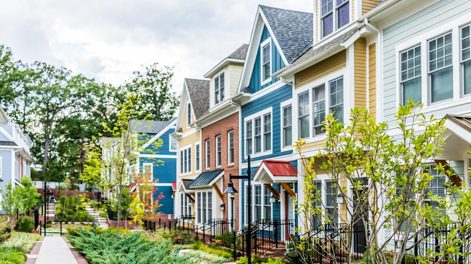 Row of colorful, red, yellow, blue, white, green painted residential townhouses, homes, houses with brick patio gardens in summer.