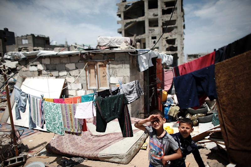 Palestinian children stand in front of their partially rebuilt home in Gaza City's Shujaiya neighbourhood on May 11, 2015 (AFP Photo/Thomas Coex)