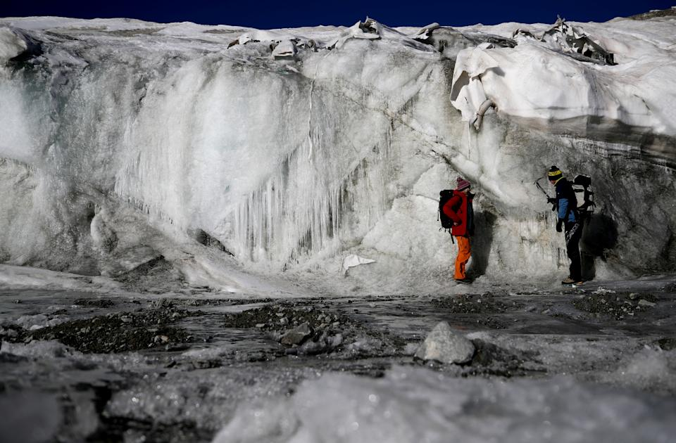 Glaciologist Andrea Fischer and environmental physicist Pascal Bohleber from the Austrian Institute for Interdisciplinary Mountain Research, inspect the thickness difference of the part of Schaufelferner glacier that is covered with a special fleece fabric protecting ice from sun and heat and the part that is not covered, near Neustift im Stubaital, Austria. (Photo: Lisi Niesner/Reuters)