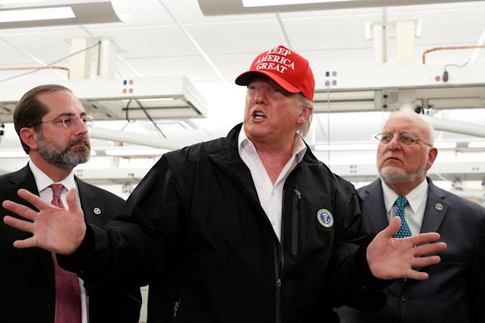 President Trump, flanked by HHS Secretary Alex Azar, left, and Centers for Disease Control and Prevention director Dr. Robert Redfield, at the CDC in Atlanta on March 6. (Tom Brenner/Reuters)