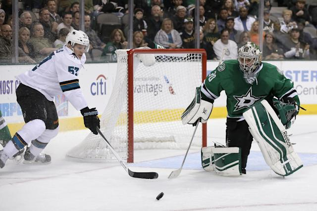 San Jose Sharks center Tommy Wingels (57) and Dallas Stars goalie Dan Ellis (30) compete for control of a loose puck in front of the net in the second period of an NHL hockey game, Thursday, Oct. 17, 2013, in Dallas. (AP Photo/Tony Gutierrez)