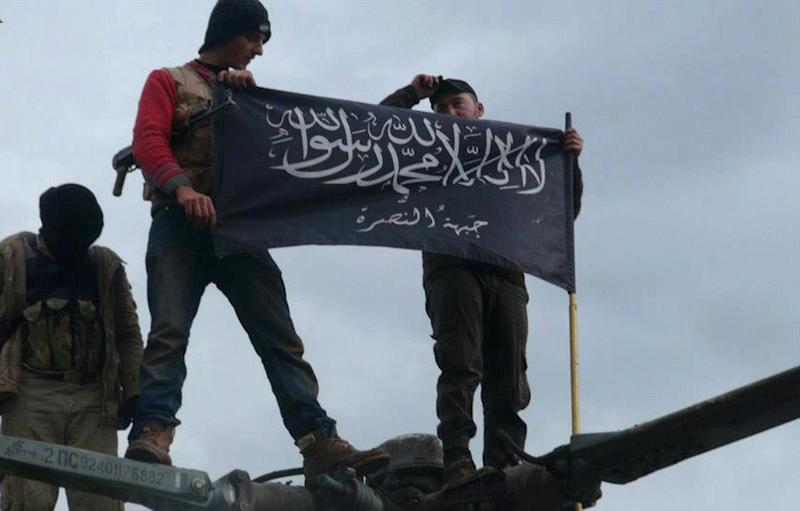 "FILE - This Friday, Jan. 11, 2013 file citizen journalism image provided by Edlib News Network, an anti-Bashar Addad group, ENN, which has been authenticated based on its contents and other AP reporting, shows rebels from al-Qaida affiliated Jabhat al-Nusra waving their brigade flag as they step on the top of a Syrian air force helicopter, at Taftanaz air base that was captured by the rebels, in Idlib province, northern Syria. A sharp increase in the number of al-Qaida linked fighters joining the fight against President Bashar Assad in Syria is threatening to spill over the borders and prompting the Jewish state to re-evaluate its policy of neutrality in the civil war next door, a senior Israeli intelligence official warned on Friday, Jan. 24, 2014. The official, who spoke on condition of anonymity because military regulations prevent him from releasing the information, claimed more than 30,000 al-Qaida linked fighters are active in Syria, more than double previous Western estimates. He did not disclose how Israel reached the figure or specify which groups were included in the count, only defining the fighters as believers in ""global jihad,"" which he said meant a mix of those linked to al-Qaida or inspired by the terror network.(AP Photo/Edlib News Network ENN, File)"