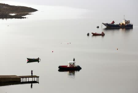 A woman stands on a jetty on the Isle of Lewis in the Outer Hebrides September 13, 2014. REUTERS/Cathal McNaughton