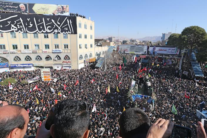 """Iranian mourners gather around a vehicle carrying the coffin of slain top general Qasem Soleimani during the final stage of funeral processions, in his hometown Kerman on January 7, 2020. - Soleimani was killed outside Baghdad airport on January 3 in a drone strike ordered by US President Donald Trump, ratcheting up tensions with arch-enemy Iran which has vowed """"severe revenge"""". The assassination of the 62-year-old heightened international concern about a new war in the volatile, oil-rich Middle East and rattled financial markets. (Photo by ATTA KENARE / AFP) (Photo by ATTA KENARE/AFP via Getty Images)"""