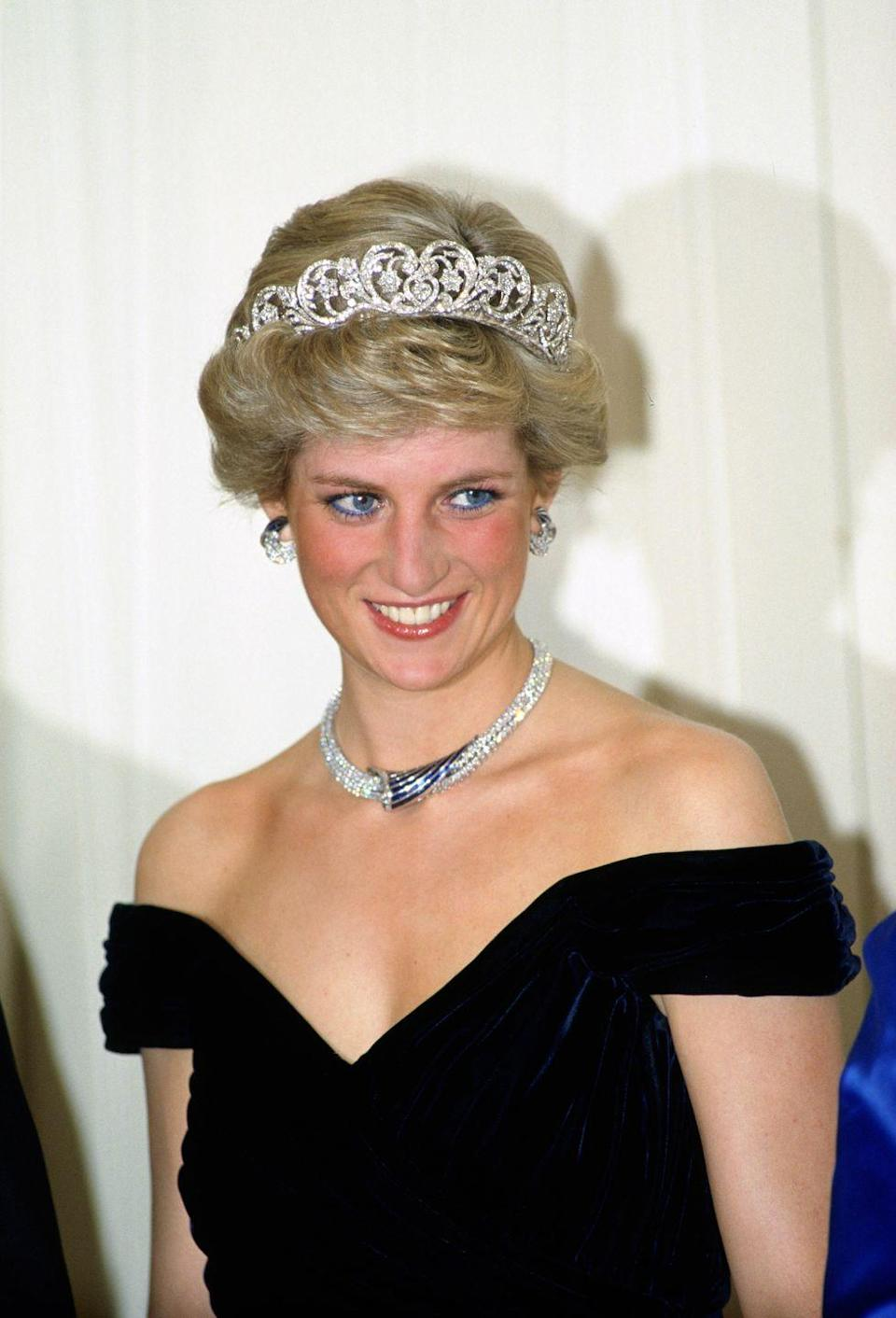 <p>At a banquet in Bonn, Germany, Princess Diana chose a black off-the-shoulder gown designed by Victor Edelstein. The princess added color with her sapphire and diamond necklace, a gift from the Sultan of Oman. She topped off the look with the Spencer tiara. </p>